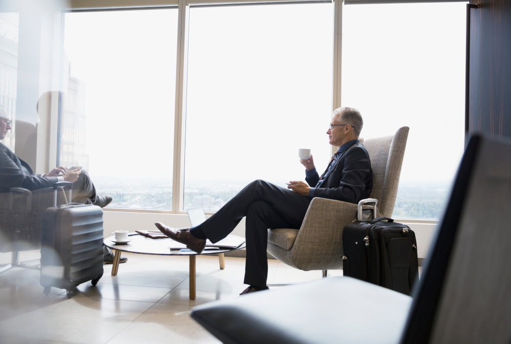 Businessman With Luggage Drinking Coffee In Airport Lounge