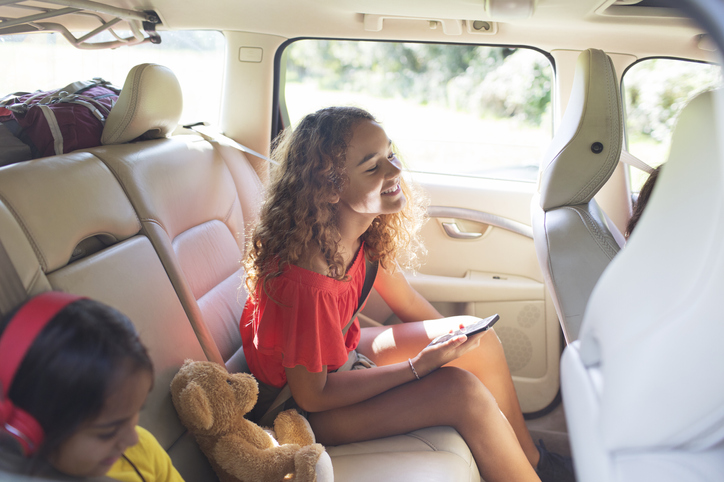 Tween Girl With Smart Phone Riding In Back Seat Of Car On Road Trip